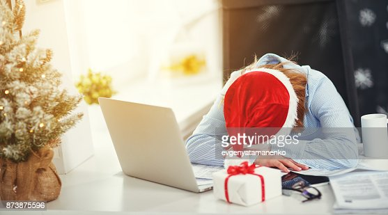 businesswoman freelancer tired, asleep working at computer at Christmas : Stock Photo