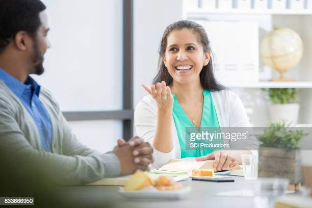 Businesswoman gestures while talking with colleague