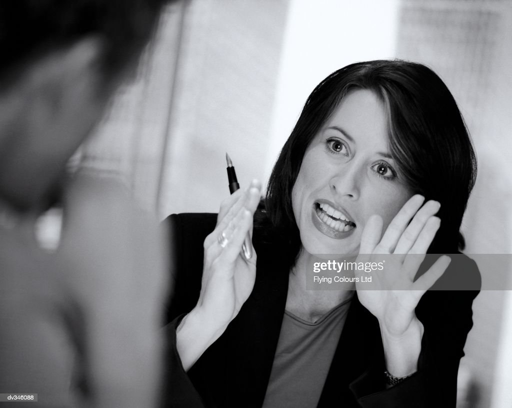 Businesswoman gesturing during discussion : Stock Photo