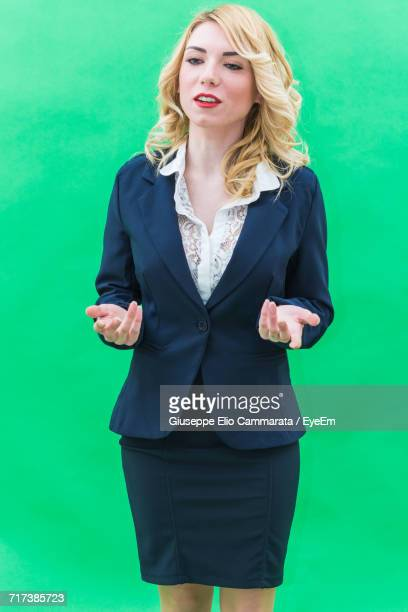 Businesswoman Gesturing While Standing Against Colored Background