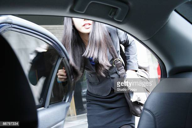 Businesswoman getting into a taxi