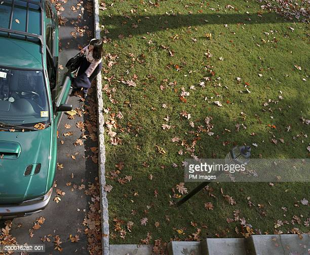 Businesswoman getting into car, elevated view