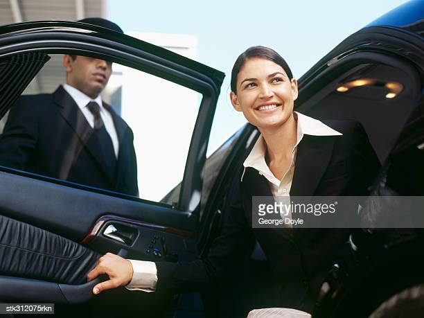 businesswoman getting out of a car and a chauffeur standing beside her