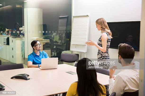 Businesswoman giving presentation at late night meeting