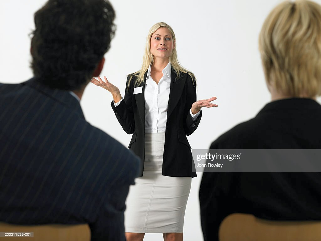 Businesswoman giving presentation holding out hands