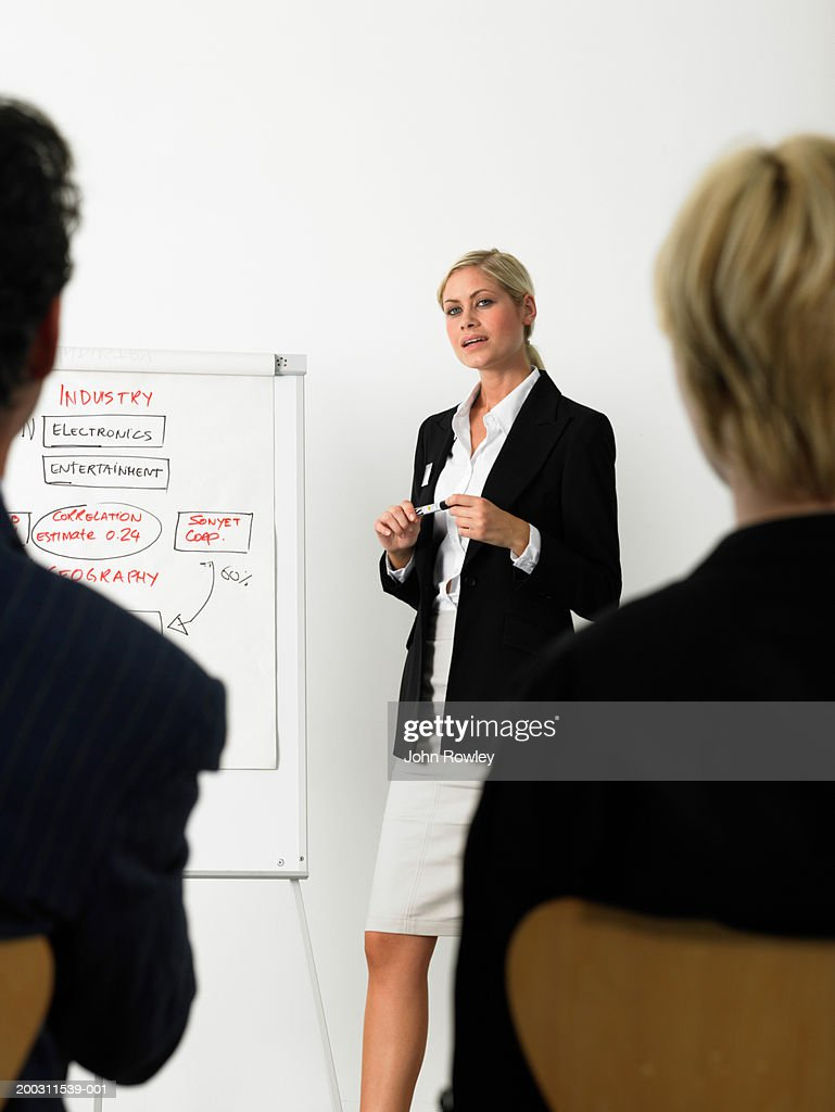 Businesswoman giving presentation standing by flipchart : Stock Photo