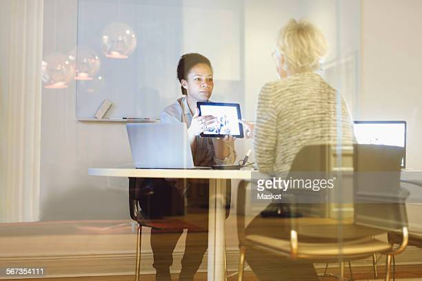 Businesswoman giving presentation to colleague on digital tablet in office