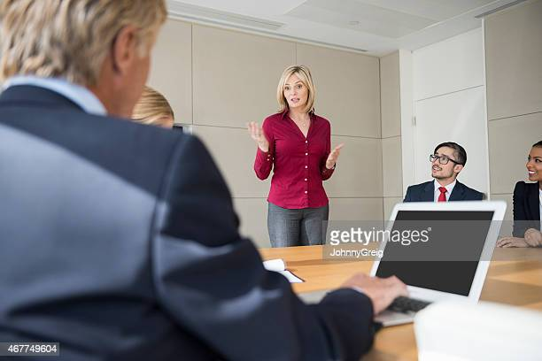 Businesswoman Giving Presentation To Colleagues At Conference Table
