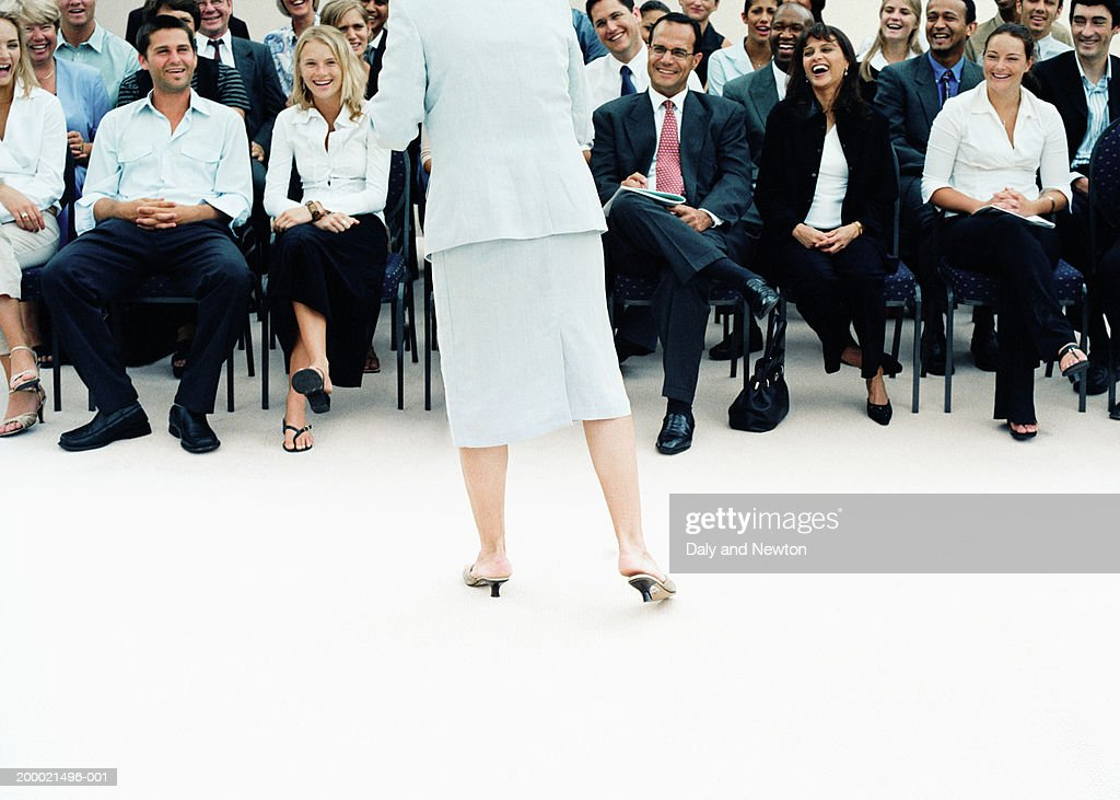 Businesswoman giving presentation to colleagues, rear view : Stock Photo