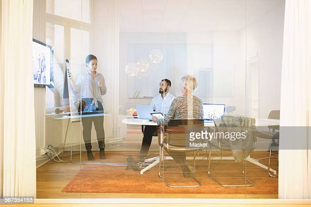 Businesswoman giving presentation to colleagues seen through window