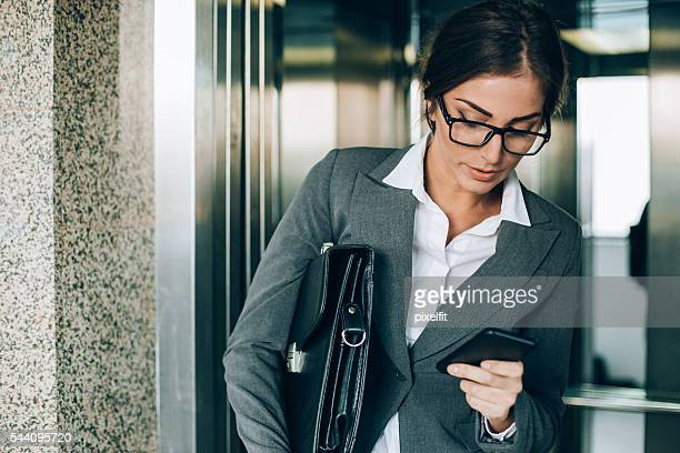Businesswoman going out of the elevator and texting