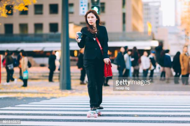 Businesswoman Going To Work On Skateboard