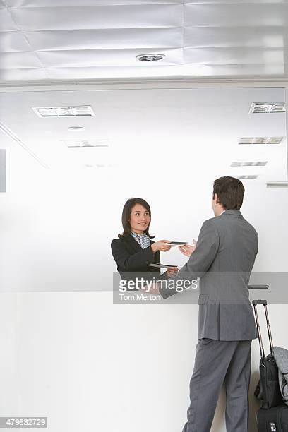 Businesswoman greeting businessman at reception desk