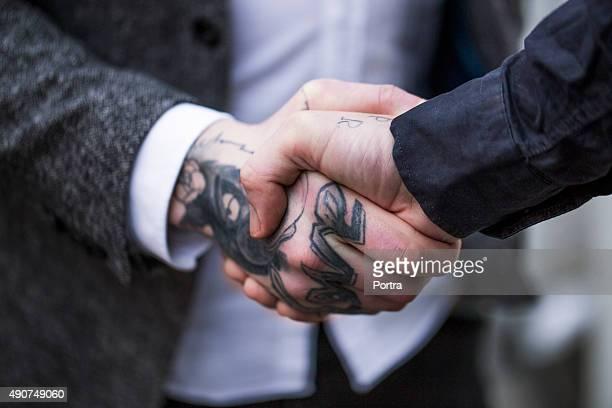 Businesswoman greeting tattooed businessman