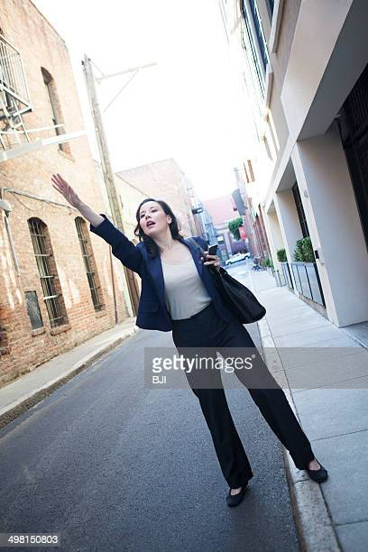 Businesswoman hailing taxi cab
