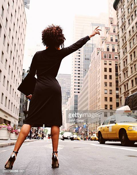 Businesswoman hailing taxi, rear view, low angle view