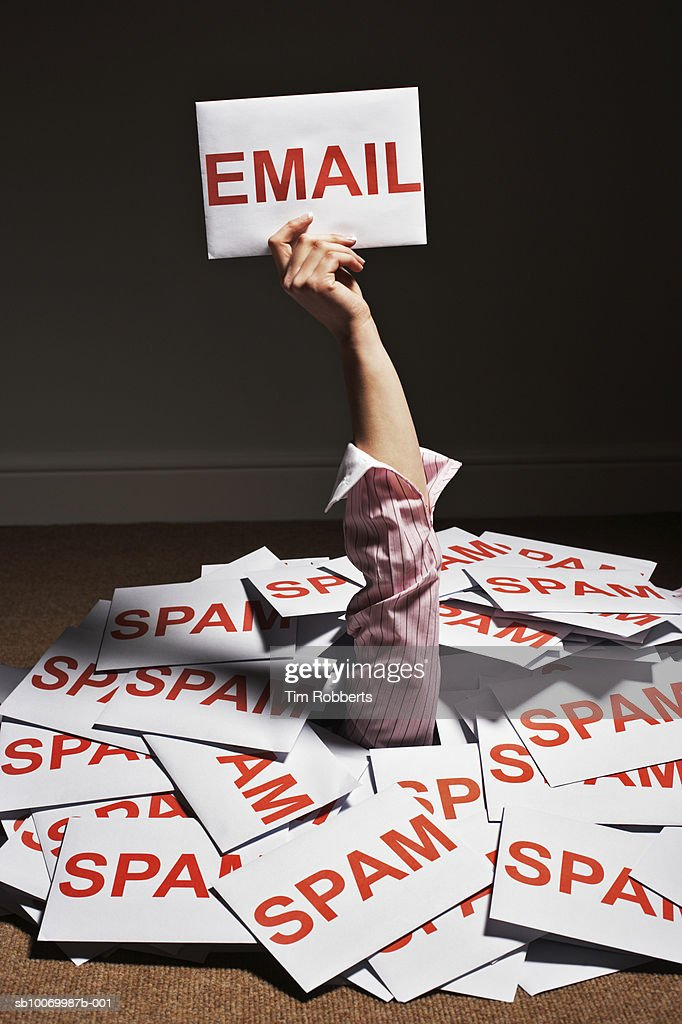 Businesswoman hand reaching out of pile of spam envelopes and holding e-mail envelope : Stock Photo