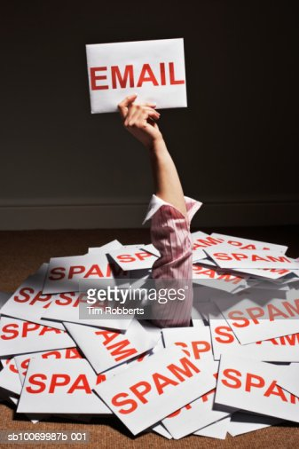 Businesswoman hand reaching out of pile of spam envelopes and holding e-mail envelope : ストックフォト