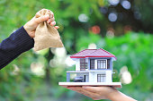 Businesswoman handed the money in bag to woman holding model house and car on natural green background, New home and Real estate trading concepts