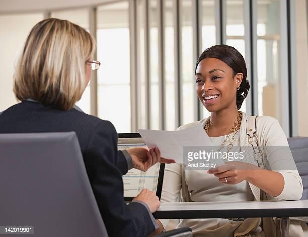Businesswoman handing paper to co-worker