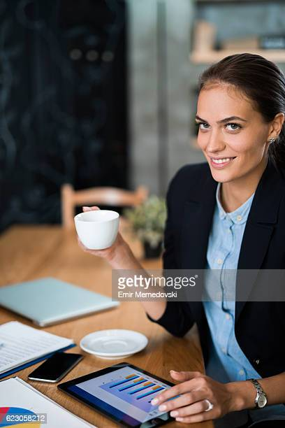 Businesswoman having a coffee break while using digital tablet.