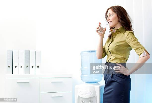 Businesswoman having drink from Water cooler.
