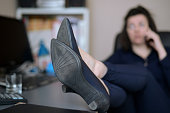 Businesswoman keeping legs on desk while making a phonecall, focus on heels with everything else in blur