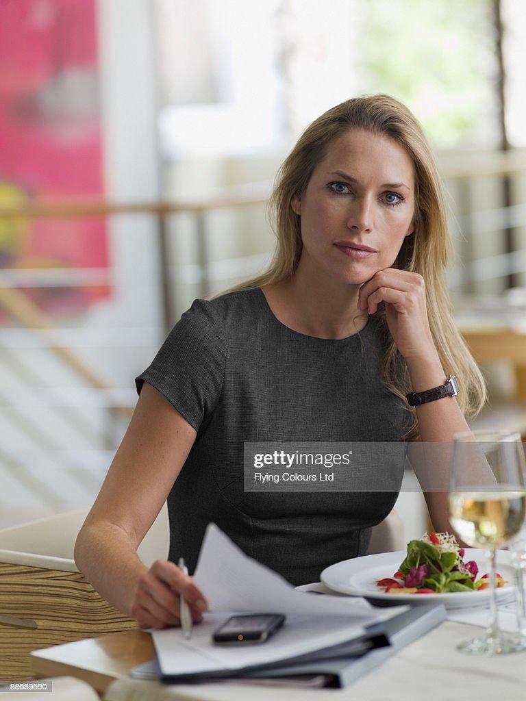 Businesswoman having working lunch : Stock Photo