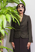 Businesswoman hiding behind plant wearing disguise