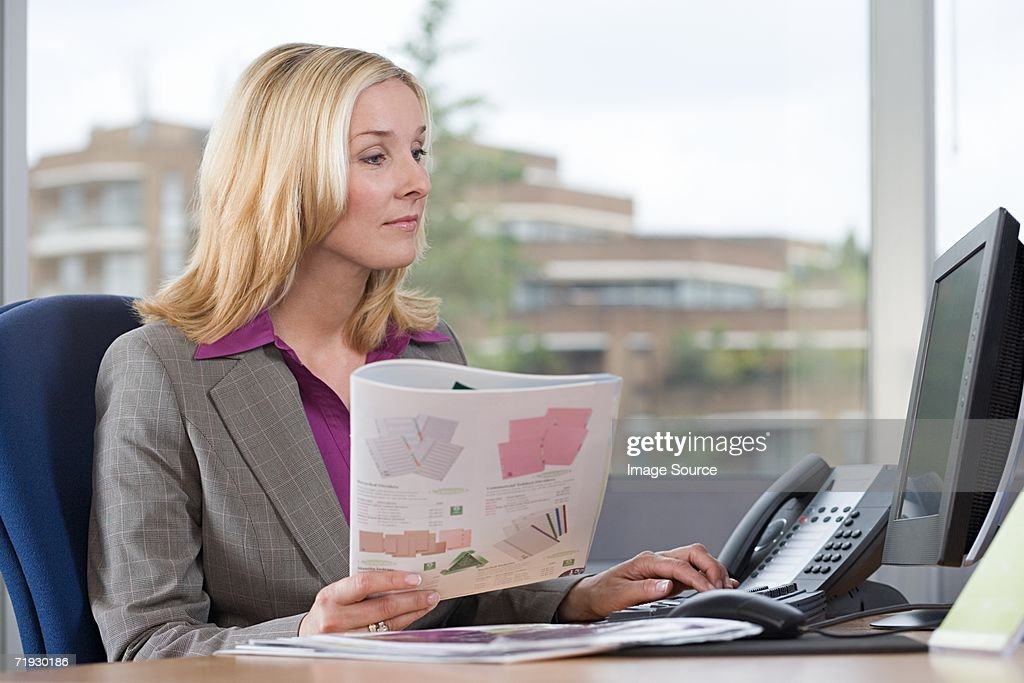 Businesswoman holding a brochure at desk : Stock Photo