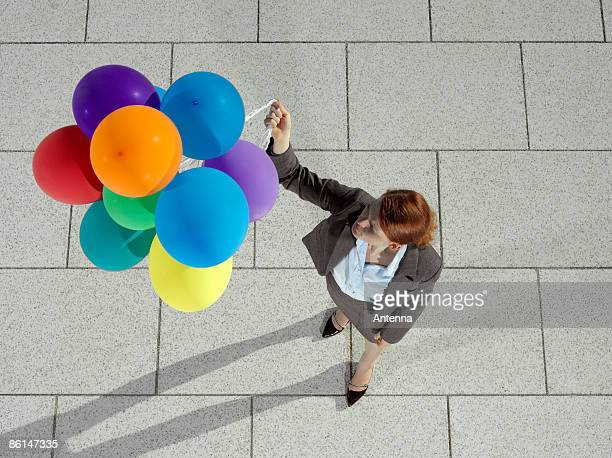 A businesswoman holding a bunch of helium balloons