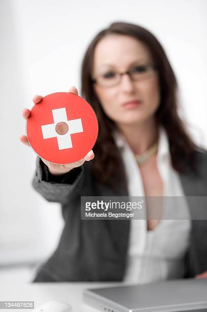 Businesswoman holding a CD with a Swiss flag