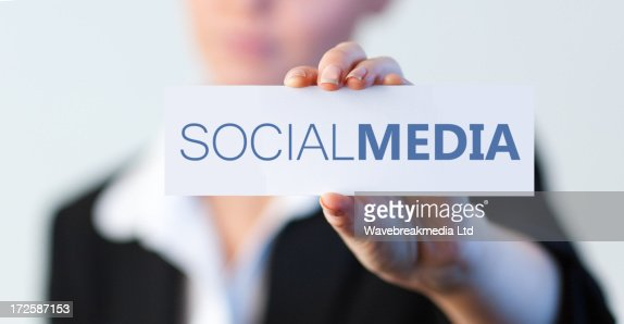 Businesswoman holding a label with social media written on it : Stock Photo