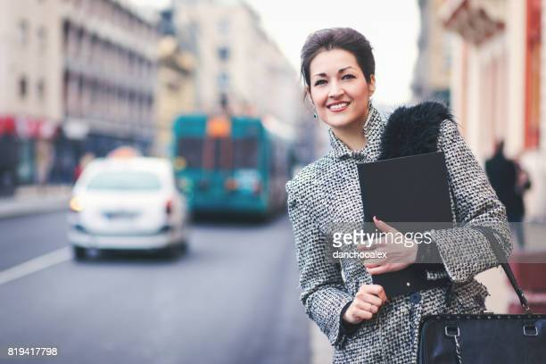 Businesswoman holding a note pad outdoors
