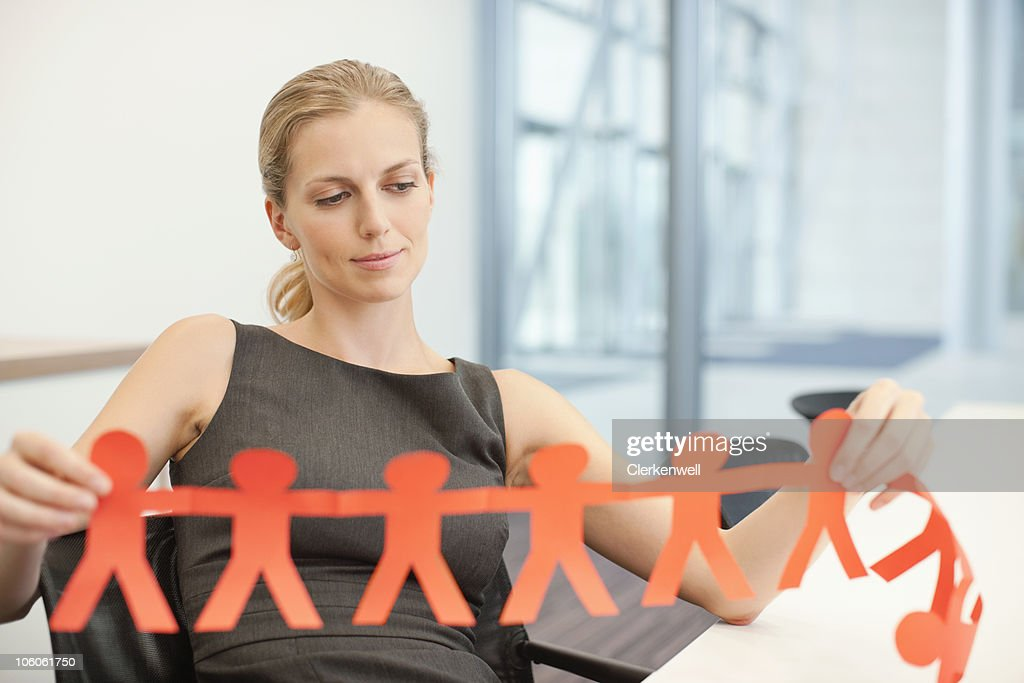 Businesswoman holding a paper cutout people : Stock Photo