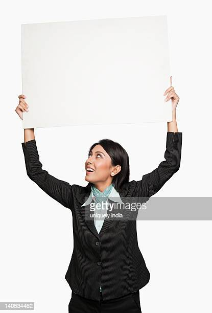 Businesswoman holding a placard over her head
