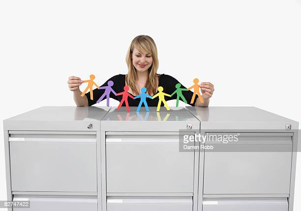 Businesswoman holding a row of paper chain figures