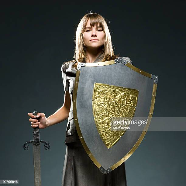 businesswoman holding a sword and a shield