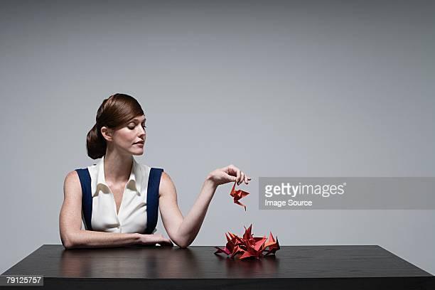 A businesswoman holding an origami bird