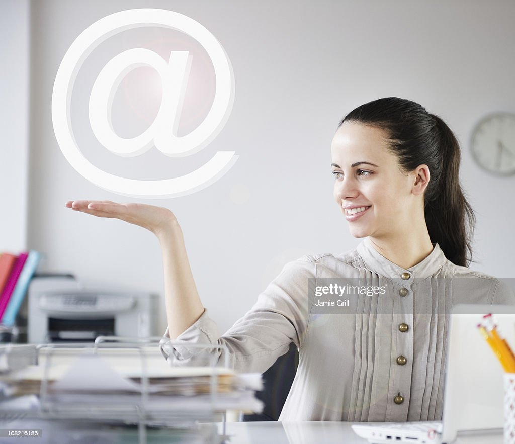 Businesswoman holding at symbol at desk : Stock Photo