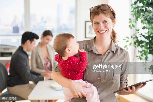 Businesswoman holding baby in office