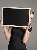 Businesswoman Holding Blank Chalkboard