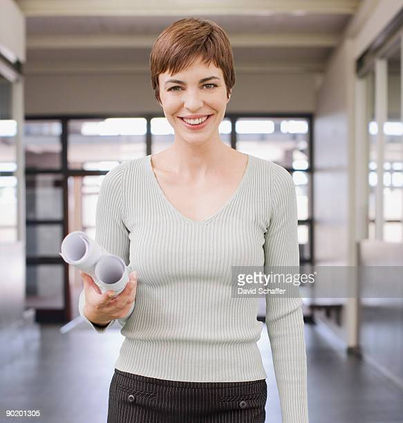 Businesswoman holding blueprints in office