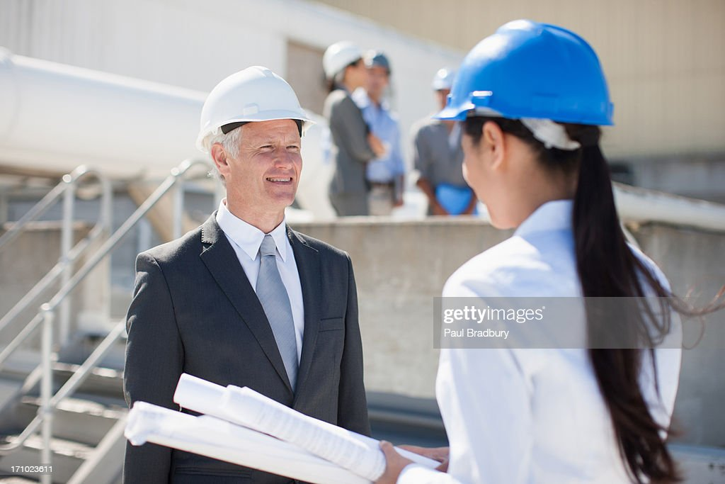 Businesswoman holding blueprints standing with co-workers : Stock Photo