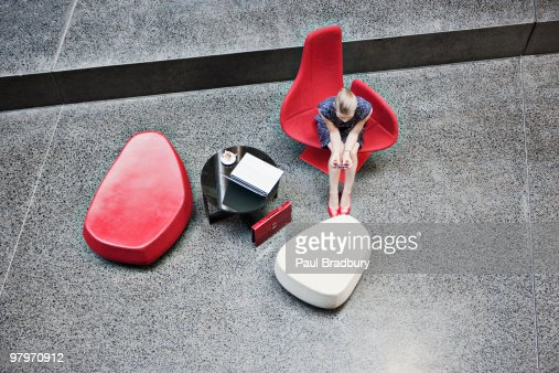 Businesswoman holding cell phone in modern lobby : Stock Photo