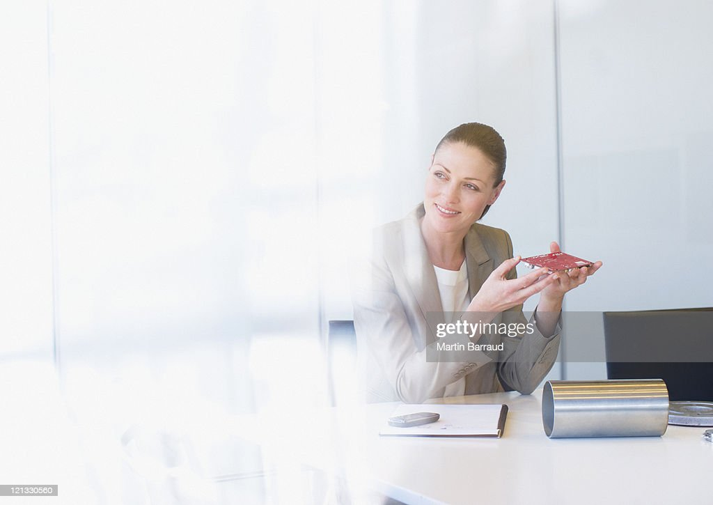 Businesswoman holding circuit board in office : Stock Photo