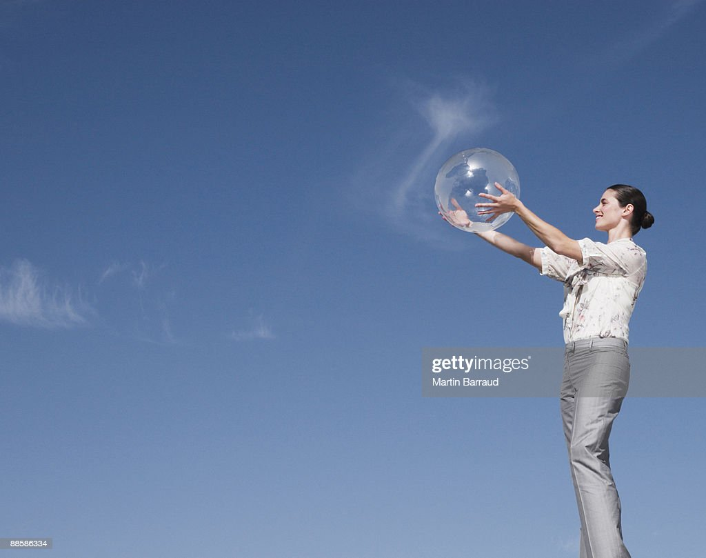 Businesswoman holding clear globe : Stock Photo
