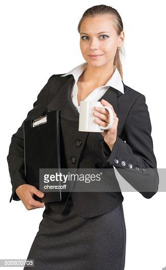 Businesswoman holding clipboard and mug : Stock Photo