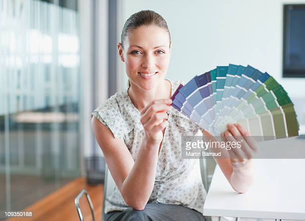 Businesswoman holding color swatches in conference room