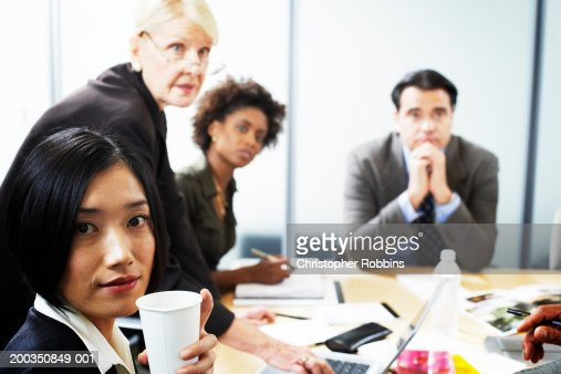 Businesswoman holding disposable cup in meeting, portrait